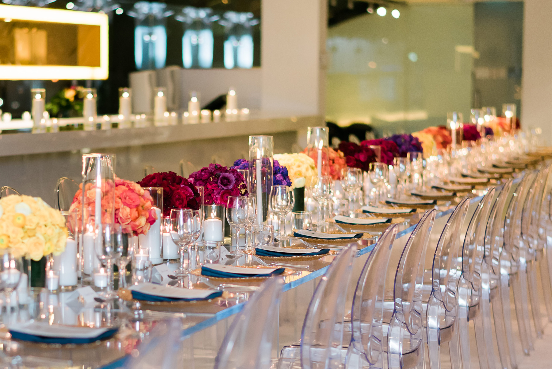 rows of candles and colorful monochromatic centerpieces